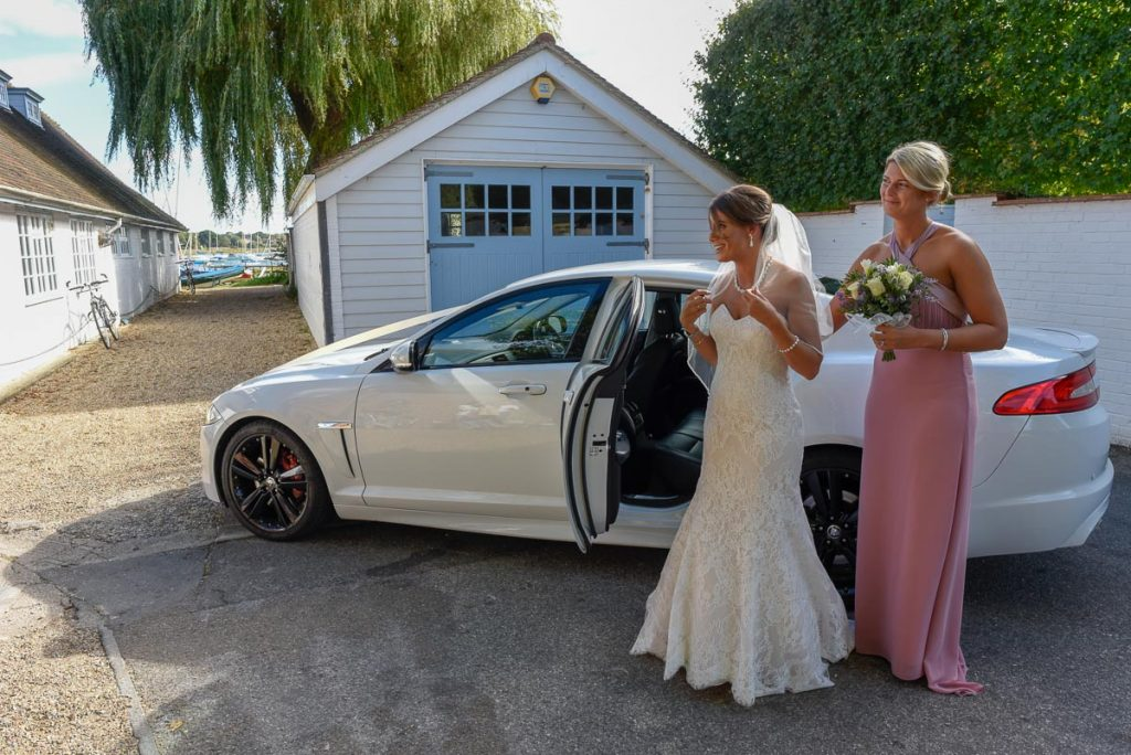 Bride arrives with the maid of honour at ichenor sailing club feeling happy but a little nervous