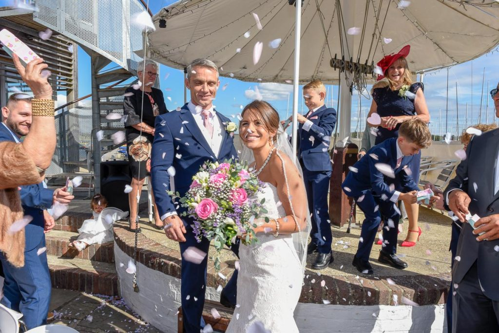 Candid photo of bride and groom looking very happy surrounded by confetti at Itchenor Sailing Club