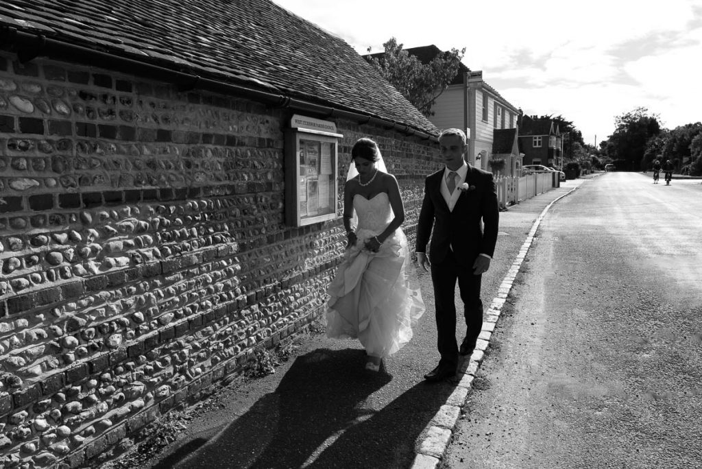 Bride and groom head back to Itchenor sailing club in the summer evening light after photo shoot by sea